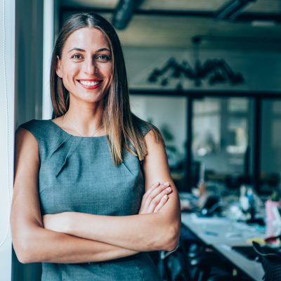 Portrait of beautiful confident smiling businesswoman leaning on a wall near the window in modern office.
