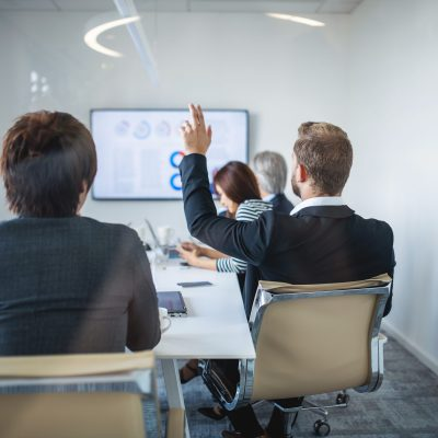 Rear view photographed through window of businesspeople participating in video conference and young male associate with hand raised.