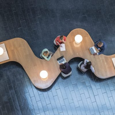 Panoramic overhead view of several business meetings going on in the communal area of a modern office building.