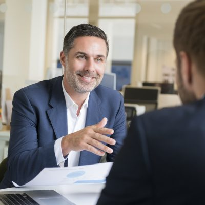 candid smiling businessman discussing with male colleague at desk in office