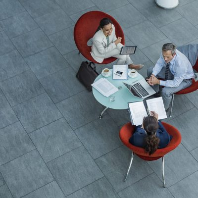 High angle view of businesspeople discussing strategy at coffee table in office