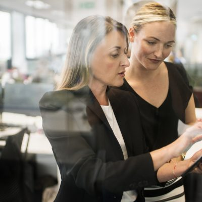 Businesswomen working together behind glass wall with reflections.