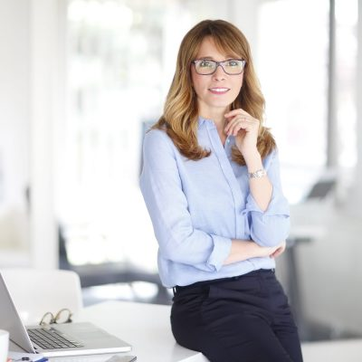 Portrait of beautiful middle aged professinal woman standing at office while looking at camera and smling.