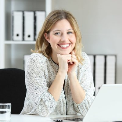 Proud office worker posing laughing and looking at side on a desktop